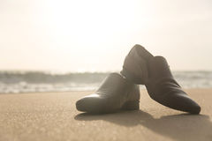 Men`s shoes on the beach at sunset. Royalty Free Stock Images