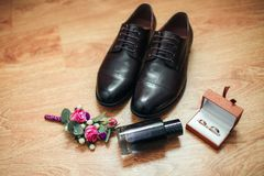 Men`s shoes boutonniere and perfume on the background of a wooden floor. Wedding details. Wedding concept Stock Photos