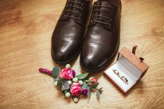 Men`s shoes boutonniere and wedding rings in a box, against the background of a wooden floor. Wedding details. Wedding concept Stock Photo
