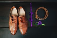 Men`s shoes from a brown leather. Men shoes, bow tie and boutonniere, top view. Men`s shoes from a brown leather. wedding concept. Men shoes, bow tie and Royalty Free Stock Photography