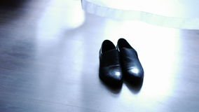 Men's shoes are on the floor next to the curtain, men's accessories.  stock footage