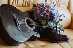 Men`s shoes, a guitar and a bouquet are on a leather sofa stock images