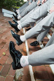 Men's shoes and pant legs. Line of men holding out their black dress shoes and one leg Royalty Free Stock Photography