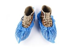 Men`s shoes in shoe covers. Men`s shoes in blue shoe covers. isolated on white background stock images