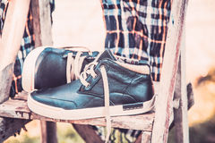 Men's shoes, wrapped in a scarf on a wooden ladder Stock Image