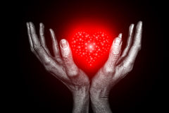 Men's silver hands holding a heart symbol Royalty Free Stock Photos