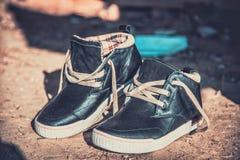 Men's sneakers in the dust on the asphalt Stock Photo
