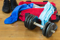 Men's sports bag with stuff inside. Men's sport red bag with things on the floor next to the dumbbell and Sneakers Stock Photography