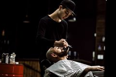 Men`s style. The barber dressed in a black clothes scissors beard of brutal man in the stylish barbershop royalty free stock photography