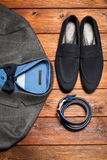 Men's suit, belt and footwear on a wooden background Royalty Free Stock Photo