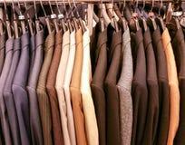 Men's suit coats on a rack. Men's suit coats in a store stock image