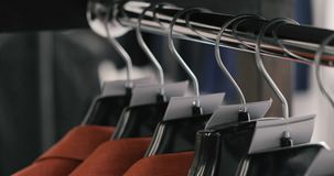 Row of men suit jackets on hangers. Collection of new beautiful clothes hanging on hangers in a shop. stock footage