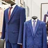 Men`s suits with shirts and ties in clothing store Royalty Free Stock Images
