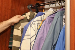 Men`s summer clothes. In the closet Stock Photos
