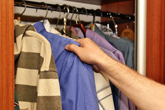 Men`s summer clothes. In the closet Stock Image