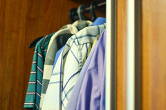 Men`s summer clothes. In the closet Stock Images