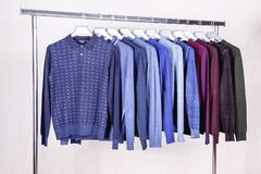Men`s sweaters on hangers Royalty Free Stock Images