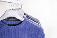 Men`s sweaters on hangers Royalty Free Stock Photos