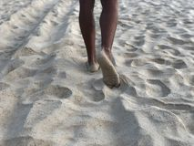 Men`s tanned legs in the white fine sand of the unique Karon beach of Phuket on the background of the sea and the Golden sunset, royalty free stock photo