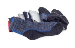 Men`s thermal sock against of pile of other socks. Gray-black men`s thermal sock on a background of pile of other different ordinary everyday socks and thermal Stock Photo