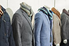Men`s tweed sport coats with scarves in clothing store Royalty Free Stock Photo