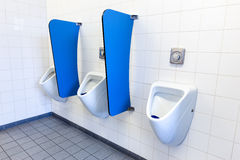 Men's urinals on white wall with blue partitions Royalty Free Stock Photos