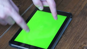 Men`s Using Tablet PC with Green Screen on Wooden Table With Various Hand Gestures stock footage