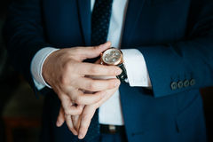 Men's watch on his hand close-up. Businessman looking at his watch on his hand, watching the time Royalty Free Stock Photos