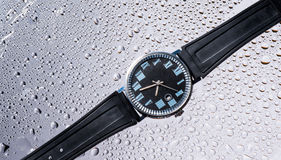 Men`s watches black wet glass Stock Images