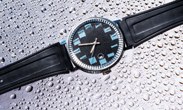 Men`s watches black wet glass Royalty Free Stock Photography