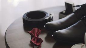Men`s wedding accessories, red butterfly, black shoes and two wedding rings in cute small white box. Slow motion stock footage