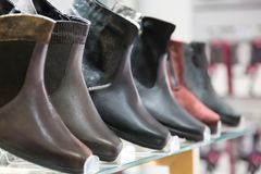 Men`s winter boots. Men`s winter boots in clothing store with selective focus.  Stock Photo