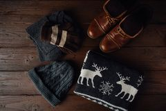 Men`s winter clothes on a brown wooden table. Royalty Free Stock Photography