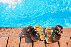 Men's and woman's flip-flops by swimming pool. Two pairs (men's and woman's) of flip-flops by sunny swimming pool royalty free stock images