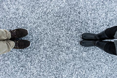 Men`s and Women boots on rough snow background. Gritty snowy covered asphalt surface. Text place. Top view. Royalty Free Stock Photos
