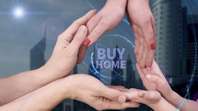 Men`s, women`s and children`s hands show a hologram Buy home. The family holds a magical inscription on the background of a modern city stock photos