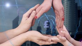 Men`s, women`s and children`s hands show a hologram Sign British Pound. The family holds a magical inscription on the background of a modern city stock photography