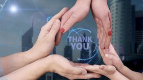 Men`s, women`s and children`s hands show a hologram Thank you. The family holds a magical inscription on the background of a modern city stock video