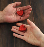 Men's and women's hands with a red heart Stock Photography