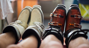 Men's and women's naked legs in ski boots Royalty Free Stock Photos