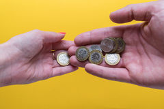 Men`s and women`s palms with coins. The man passes the coins to the woman. Lack of money. Family budget Stock Photos