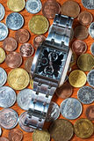 Men's wrist watch on metal coins Royalty Free Stock Images