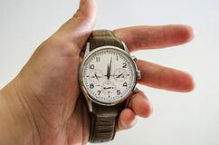 Men`s, wristwatches with brown strap in hand, isolated on white background. Close-up. stock image