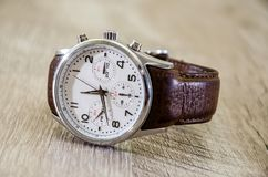 Men`s, wristwatches with brown strap on wooden background stock images