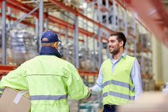 Men in safety vests shaking hands at warehouse Royalty Free Stock Photography