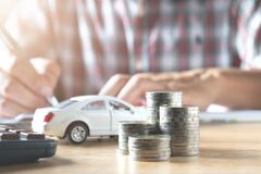 Men are Saint documents about cars with some coins calculator. And car toy on desk royalty free stock images