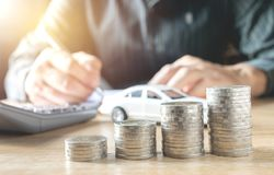 Men are Saint documents about cars with some coins calculator. And car toy on desk stock photography