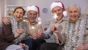 Men in Santa Claus hats and women wrapped in tinsels holding sparklers, New Year. Stock footage stock footage
