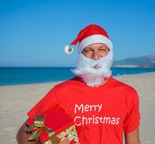 Men in santa hat. Portrait of young man in Santa hat with gift on tropical vacation Stock Image