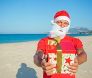 Men in santa hat. Young man in Santa hat with gift on tropical vacation Royalty Free Stock Photography